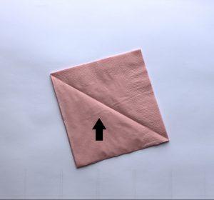 2) Die Serviettenschichten trotzdem so übereinander liegen lassen, als wäre die Serviette noch ganz. Diese jetzt diagonal in der Mitte falten, sodass ein Dreieck entsteht.